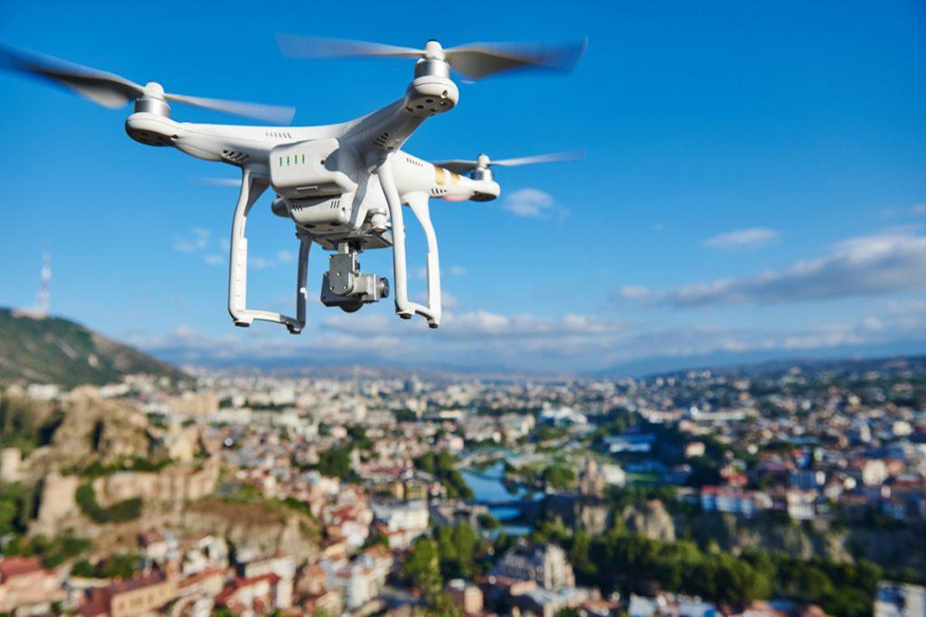 che cosa è un drone, foto di undrone che sorvola un paesaggio